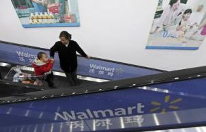 A customer looks at her child on a shopping trolley as they take an escalator at a Wal-Mart supermarket in Wuhan