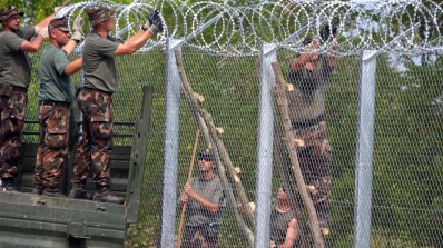 A picture is taken on July 18, 2015 shows soldiers of the Hungarian Army's technical unit finish the first completed elements of the 150 meter-long metal fence at the Hungarian-Serbian border nearby Morahalom village. Defense Minister Csaba Hende said that 900 people would work simultaneously to install the fence which is planned to be 4 meters (13 feet) high along the 175-kilometer (109-mile) border between Hungary and Serbia. Over the last two years, Hungary has been one of the main routes for people hoping to cross into Austria and Germany, most coming from Afghanistan, Iraq, Syria and Kosovo. Hungary's defense minister says that a fence on the border with Serbia to stem the flow of migrants and refugees will be built by Nov. 30.  AFP PHOTO / CSABA SEGESVARI        (Photo credit should read CSABA SEGESVARI/AFP/Getty Images)