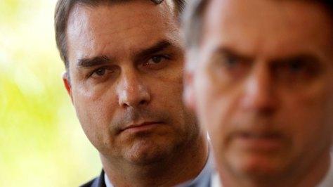 FILE PHOTO: Flavio Bolsonaro, son of Brazil's President Jair Bolsonaro is seen behind him at the transition government building in Brasilia
