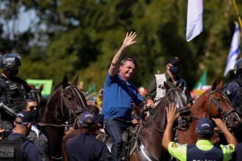O presidente Jair Bolsonaro cumprimenta apoiadores na frente do Palácio do Planalto
